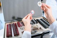 Подрезанный взгляд офтальмолога держа объективы стоковое фото rf