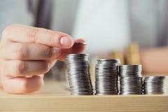 Подрезанный взгляд персоны штабелируя монетки на таблице Стоковые Фото
