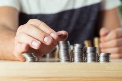 Подрезанный взгляд персоны штабелируя монетки на таблице Стоковое Изображение