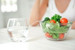 Подрезанный портрет молодой усмехаясь женщины есть свежий салат в белой комнате Стоковые Изображения RF
