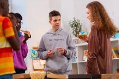 4 подростка есть yummy пиццу после активного метода мозгового штурма стоковые фото