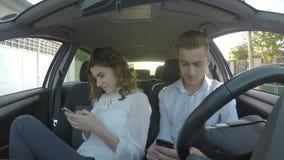 2 подростка используя социальные средства массовой информации на их умных телефонах пока сидящ в автомобильном сток-видео