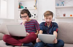 2 подростка с устройствами и наушниками на кресле дома Стоковые Изображения