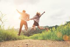 Подростки битника скача на поле цветка, счастливое время, наслаждаются l Стоковое Изображение RF