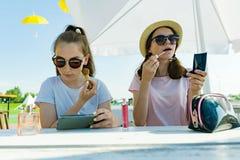 Подростки девушек имея потеху, губы цвета, макетируют, использовать parfum Кафе улицы лета, рекреационная зона, предпосылка парка стоковые фото