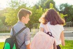 Подростки детей идут к школе, заднему взгляду Outdoors, подросток с рюкзаками стоковое изображение