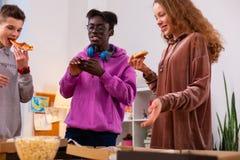 Подростки есть на вынос пиццу после изучать совместно стоковые фотографии rf