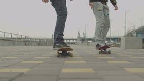 Подростки ехать скейтборды на тротуаре в городе