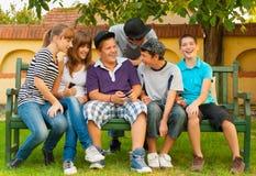 Подростки и девушки имея потеху в саде Стоковая Фотография