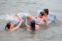 Подростки и девушки имея потеху с тюфяком Стоковая Фотография