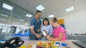 Подростки и мужской инструктор наблюдают quadcopter видеоматериал