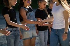 Подростки объединяются в команду один другого приветствию с трясут руки outdoors в солнечном дне стоковое фото