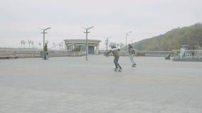 Подростки свертывая и поворачивая дальше скейтборды