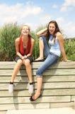 Подростки сидят снаружи Стоковые Изображения