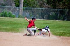 Подростковая короткая остановка бейсбола маркируя игрока вне на второй базе Стоковые Фото