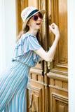 Подросткового возраста девушка в платье комбинезона стучает на винтажной двери стоковая фотография