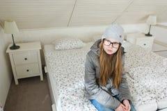 Подросткового возраста девушка сидя на утре кровати перед идти обучить - ленивый начать рабочий день - утра трудна стоковые фотографии rf