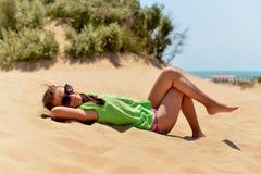 подростковое девушки пляжа лежа песочное стоковые фото