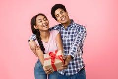 Подростковое ликование пар, протягивая присутствующую коробку к камере стоковая фотография rf