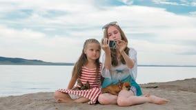 2 подростковое сидят на песчаном пляже, на интернете в телефоне Стоковое фото RF