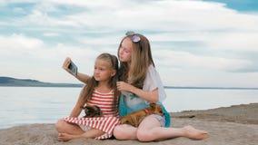 2 подростковое сидят на песчаном пляже, на интернете в телефоне Стоковые Изображения