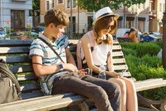 Подростковые друзья девушка и мальчик сидя на стенде в городе, усмехающся, говорить, смотря в телефоне Приятельство и концепция л стоковое фото