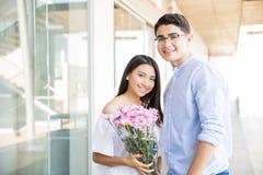Подростковые пары с датировка букета цветка в торговом центре стоковое фото