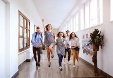 Подростковые студенты в зале средней школы скача высоко стоковые фото