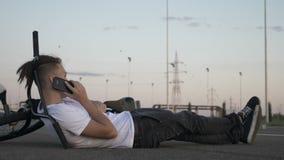 Подростковый битник кладя на том основании используя smartphone пока велосипедисты скачут над им выполняя опасные эффектные высту акции видеоматериалы