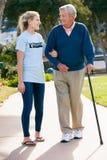Подростковый волонтер помогая старшему человеку ToWalk Стоковые Фотографии RF
