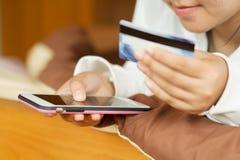 Подростковый женщины держа умный телефон с кредитной карточкой пока ходящ по магазинам на интернете дома стоковое фото