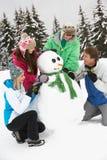Подростковый снеговик здания семьи на празднике лыжи Стоковая Фотография RF