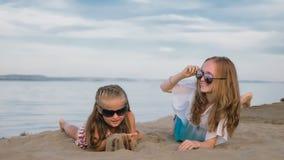 2 подростковых дет сидят на пляже Стоковая Фотография