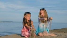 2 подростковых дет сидят на пляже Стоковое Изображение RF