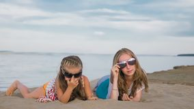 2 подростковых дет сидят на пляже Стоковые Фотографии RF