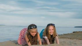 2 подростковых дет сидят на пляже Стоковые Фото