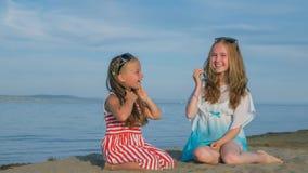 2 подростковых дет сидят на пляже Стоковая Фотография RF