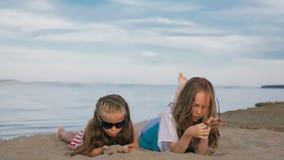 2 подростковых дет сидят на пляже Стоковое Изображение