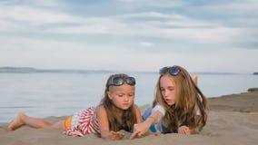 2 подростковых дет сидят на пляже Стоковое Фото