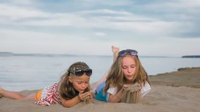 2 подростковых дет сидят на пляже Стоковые Изображения
