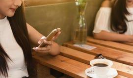 2 подростковых женщины встречают в игре смартфона пользы кофейни социальной стоковые фотографии rf