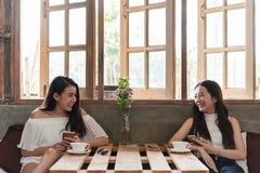 2 подростковых женщины встречают в игре смартфона пользы кофейни социальной стоковая фотография rf