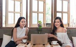 2 подростковых женщины встречают в смартфоне и ноутбуке пользы кофейни стоковые изображения