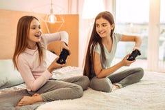 2 подростковых сестры играя видеоигру восторженно стоковые изображения
