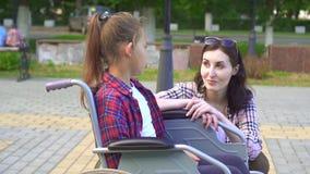 Подросток выведенный из строя в кресло-коляске говоря к девушке Медленный mo видеоматериал