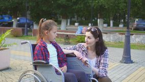 Подросток выведенный из строя в кресло-коляске говоря к девушке Стоковое Изображение