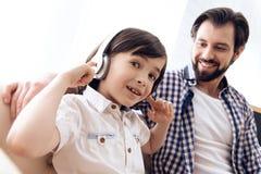 Подросток в наушниках слушает музыку, сидя со счастливым отцом на кресле стоковое изображение rf