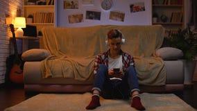 Подросток в наушниках слушая музыку, беседуя с друзьями по телефону, устройство сток-видео
