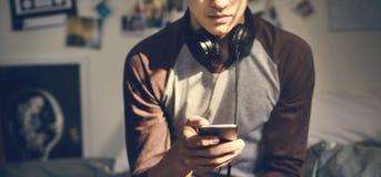Подросток в спальне слушая к музыке через его smartpho стоковые фотографии rf