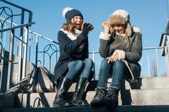 Подросток девушек кричит в бумажный стаканчик мегафона, одетый в зиме стоковое фото